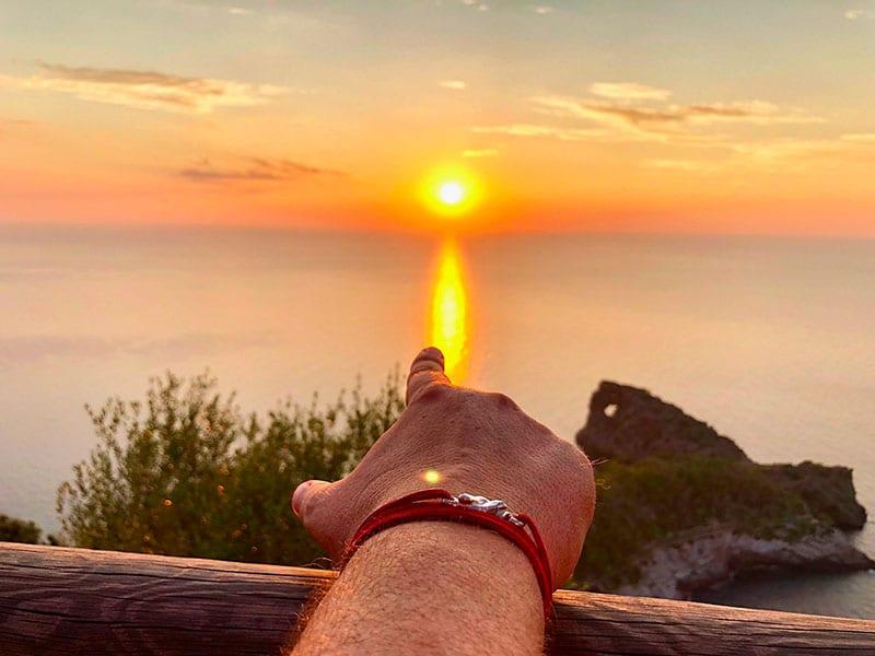 Pulsera de la leyenda del hilo rojo del destino señalando la puesta de sol