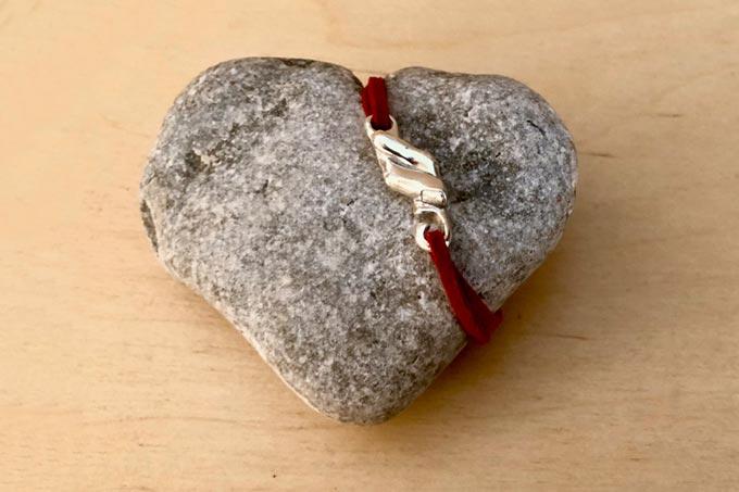 Pulsera del hilo rojo de destino sobre una piedra