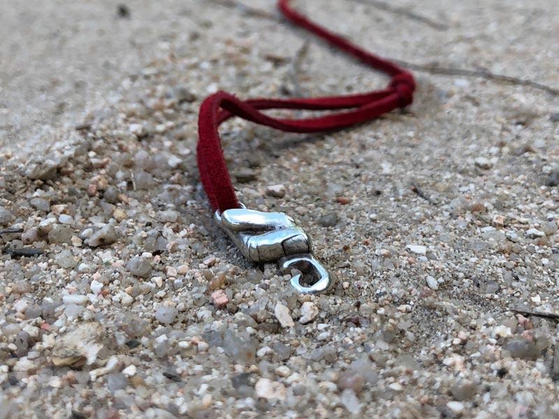 Pulsera del hilo rojo del destino en la arena